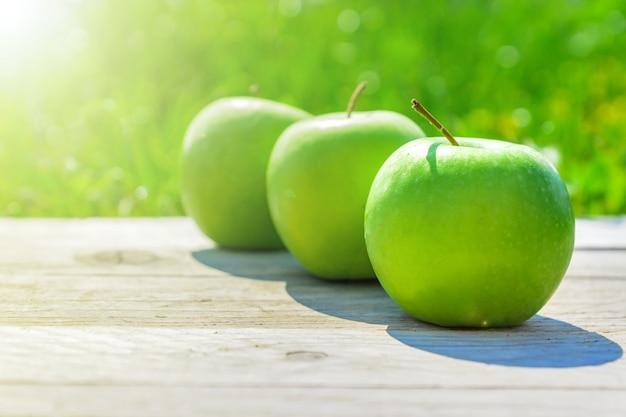 Pommes Vertes Fraîchement Coupées Sur Table En Bois Sur L'herbe Verte Photo Premium
