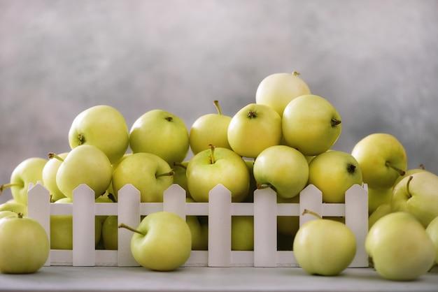 Pommes vertes fraîches dans une boîte en bois sur gris clair. espace libre Photo Premium