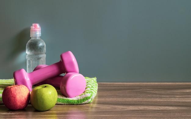 Pommes vertes et rouges, haltères et bouteille d'eau sur le plancher de bois avec espace copie. Photo Premium