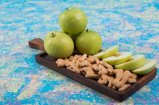 Pommes Vertes En Tranches Avec Des Craquelins Sur La Planche De Bois, Vue D'angle. Photo gratuit