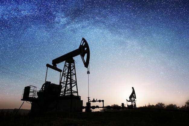 Pompe à huile sur le champ de pétrole dans la nuit Photo Premium