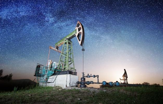 Les pompes à huile travaillent sur le champ pétrolifère dans la soirée Photo Premium
