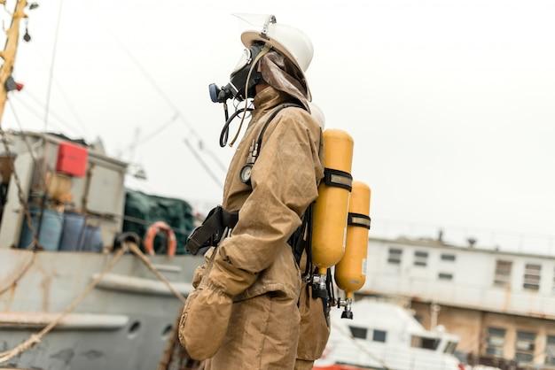 Pompier dans le port de la mer avec du matériel sur une formation pour arrêter le feu Photo Premium