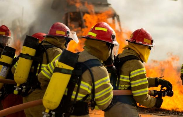 Pompier faisant du travail d'équipe contre le feu Photo Premium