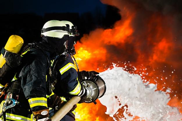 Pompier, pompiers éteignant un grand incendie Photo Premium
