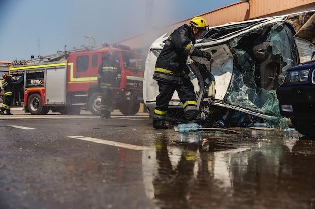 Les Pompiers En Action. Pompiers éteignant Le Feu Et Essayant De Retourner La Voiture Accidentée Dans Un Accident De Voiture. Photo Premium