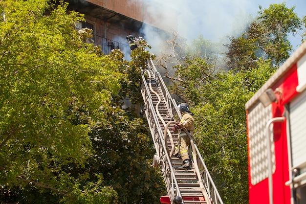 Les pompiers éteignent un incendie dans un immeuble résidentiel de grande hauteur. Photo Premium