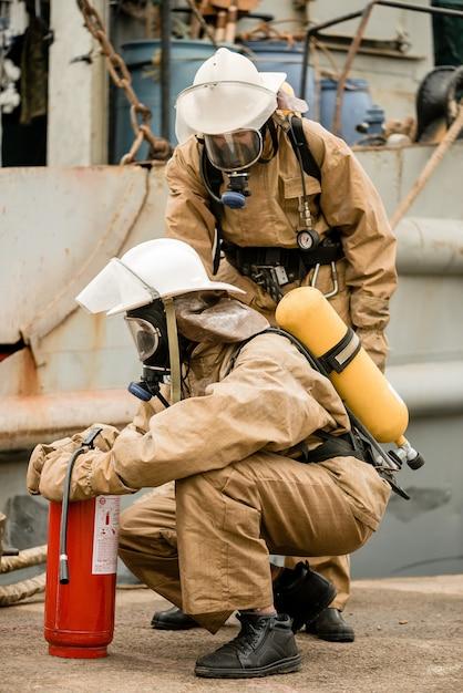 Les pompiers vérifient l'équipement et l'extincteur lors d'une formation sur la manière d'arrêter un incendie dans un port maritime Photo Premium