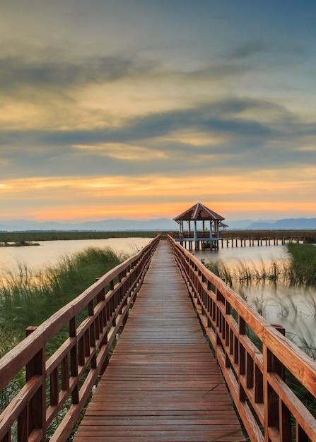 Pont en bois dans le lac lotus à l'heure du coucher du soleil au parc national de khao sam roi yot, thaïlande Photo Premium