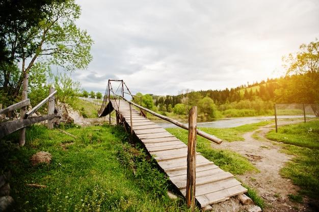 Pont suspendu de montagne en bois de la rivière des carpates Photo Premium