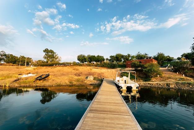 Ponton en bois avec bateau amarré et reflets sur l'eau du lac Photo Premium