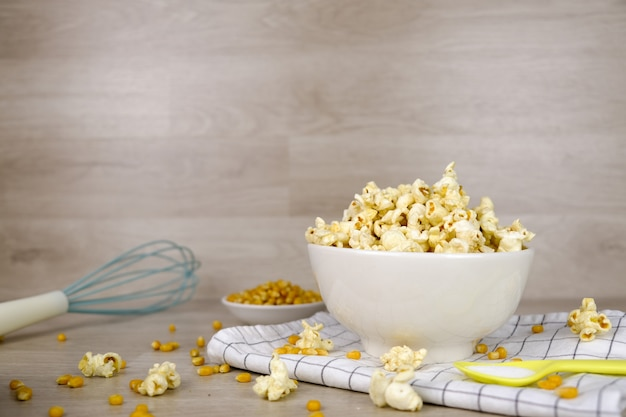 Pop-corn dans un bol blanc avec cuillère pastel, sel, batteur à main et graines de maïs sur fond de bois Photo Premium