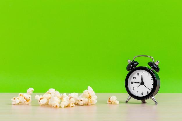 Pop-corn Et Petit Réveil Sur Une Surface Verte Pastel Concept Créatif Minimal Espace Pour Copie Photo Premium