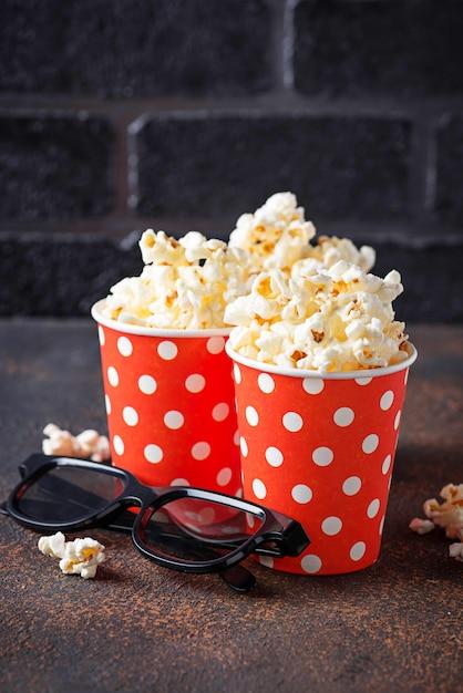 Popcorn avec des lunettes 3d sur fond sombre Photo Premium