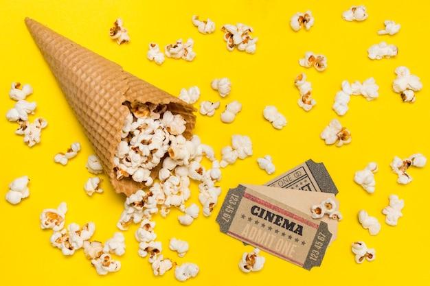 Popcorns renversant du cône de gaufres avec des billets de cinéma sur fond jaune Photo gratuit