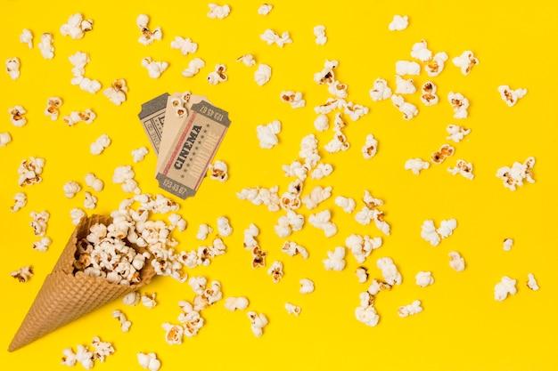 Popcorns renversés du cône de gaufres avec billet de cinéma Photo gratuit