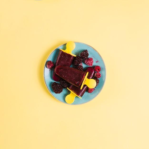 Popsicles avec des baies sur la plaque Photo gratuit