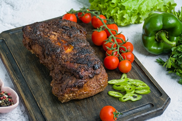 Porc au four haché dans une sauce aux noix et à la menthe sur une planche à découper avec des herbes fraîches et des légumes. Photo Premium