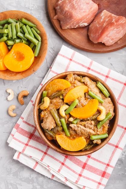 Porc frit avec des pêches, des noix de cajou et des haricots verts sur un fond de béton noir Photo Premium