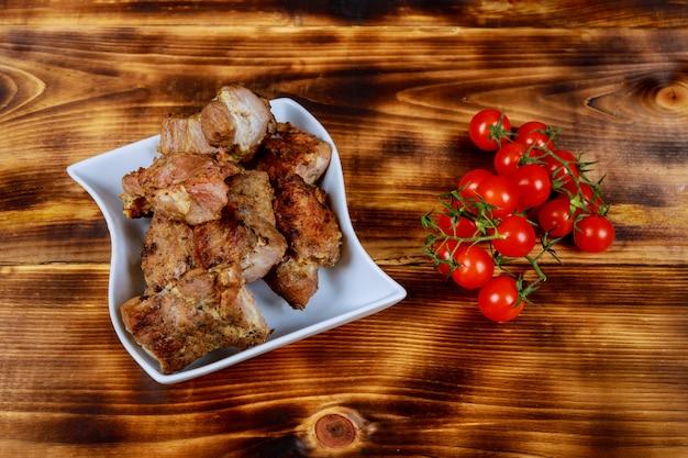 Porc shashlyk sur des brochettes sur une planche de bois sombre avec des tomates, des épinards et des sauces Photo Premium