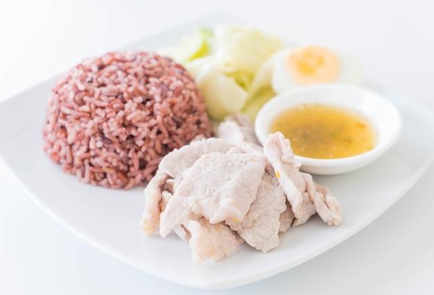Porc à la vapeur avec sauce épicée et citron au riz aux baies Photo gratuit