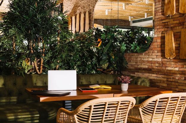 Portable; tablette numérique; livre et plante en pot sur une table en bois dans le restaurant Photo gratuit