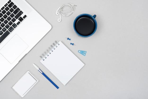 Portable; tasse à café avec papeterie de bureau et écouteurs sur un bureau gris Photo gratuit