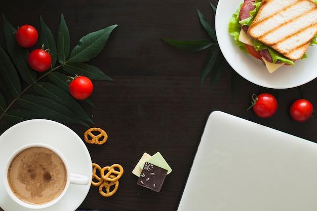 Portable; tomates; sandwich; morceaux de chocolat; bretzels et tasse à café sur fond noir Photo gratuit