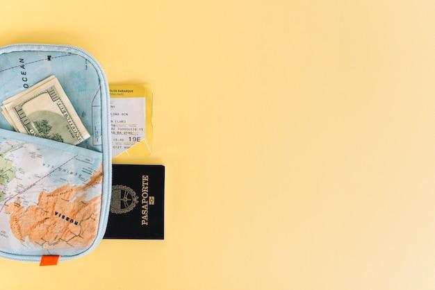 Porte-cartes avec monnaie; passeport et billet sur fond jaune Photo gratuit