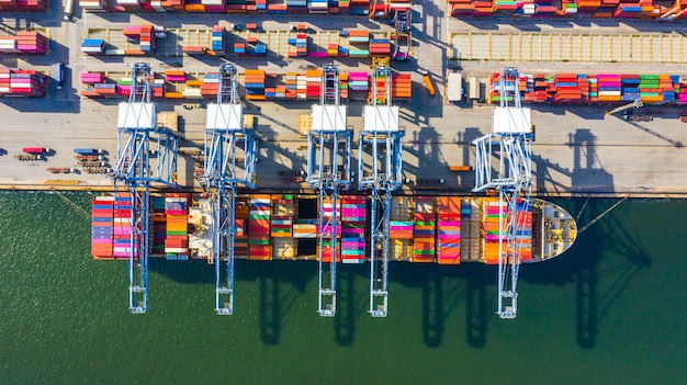 Porte-conteneurs de chargement et de déchargement dans le port de haute mer, vue de dessus aérienne du transport de fret logistique d'affaires d'importation et d'exportation Photo Premium
