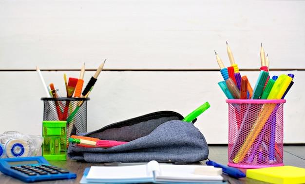 Porte-crayons et fournitures scolaires sur une table en bois Photo Premium