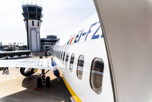 Porte ouverte d'un avion garé pendant le débarquement des passagers. Photo Premium