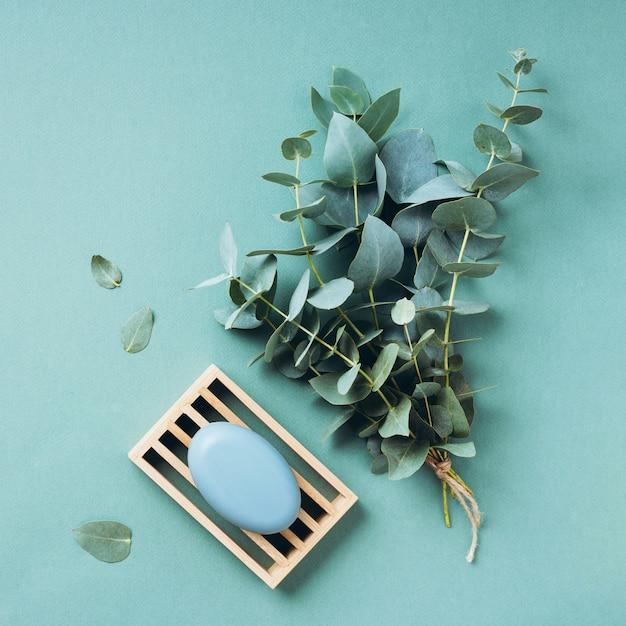 Porte-savon en bois, savon, eucalyptus sur fond vert. zéro déchet, outils de salle de bains organiques naturels. Photo Premium