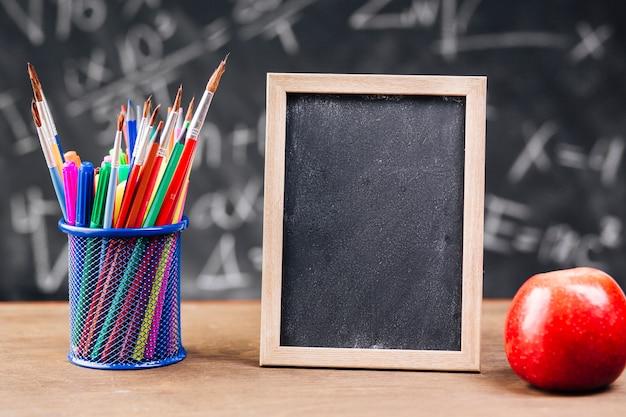 Porte-stylo et tableau blanc avec pomme posés sur le bureau Photo gratuit