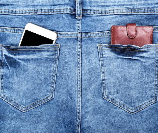 Portefeuille en cuir marron et smartphone blanc avec un écran noir vide dans la poche arrière Photo Premium
