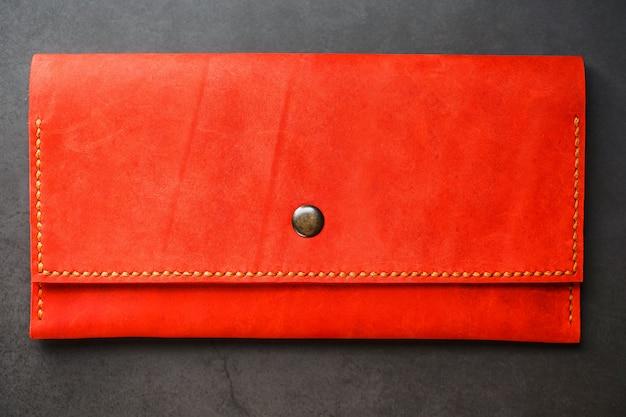 Portefeuille en cuir rouge sur une vue de dessus de fond sombre. gros plan, détails de sac à main, rivet et firmware Photo Premium