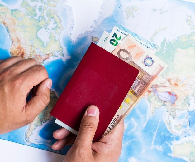 Portefeuille fermé avec euros et carte du monde Photo gratuit