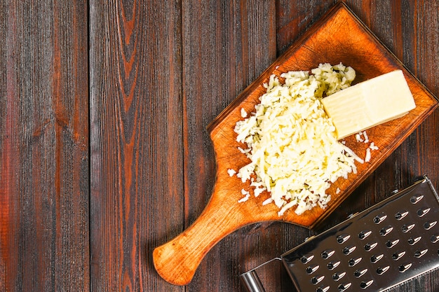 Portion de fromage cheddar râpé sur une table en bois rustique. Photo Premium