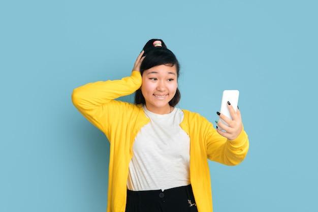 Portrait D'adolescent Asiatique Isolé Sur Fond Bleu Studio Photo gratuit
