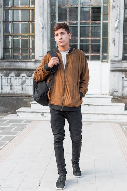 Portrait, adolescent, main, poche, sac, épaule, marche, devant, bâtiment Photo gratuit