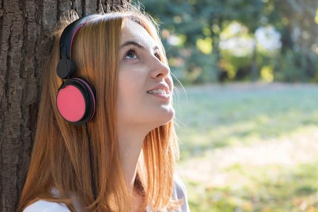 Portrait d'adolescente aux cheveux rouges, écouter de la musique dans les gros écouteurs roses se penchant à l'extérieur pour un arbre. Photo Premium