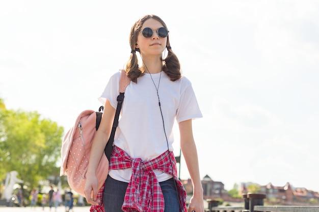 Portrait d'adolescente étudiante avec sac à dos en plein air dans la rue souriant heureux de retourner à l'école Photo Premium
