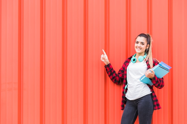 Portrait d'une adolescente heureuse, tenant des livres à la main avec un casque autour du cou, pointant le doigt contre un mur orange Photo gratuit