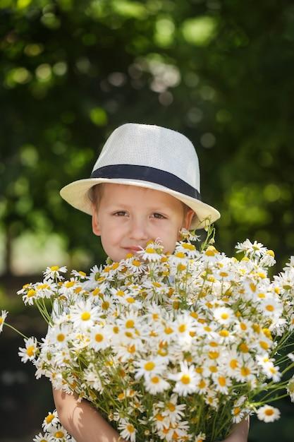 Portrait adorable garçon au chapeau avec gros bouquet blanc de marguerites Photo Premium