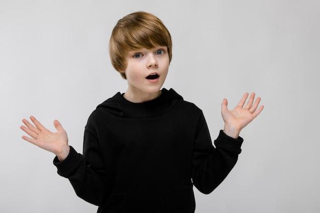 Portrait de l'adorable petit garçon surpris avec la bouche ouverte et les bras ouverts Photo Premium