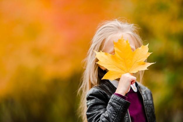 Portrait d'une adorable petite fille avec un bouquet de feuilles jaunes en automne en scooter Photo Premium