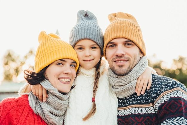 Portrait de l'adorable petite fille porte bonnet et chandail se dresse entre les parents, embrasse-les Photo Premium