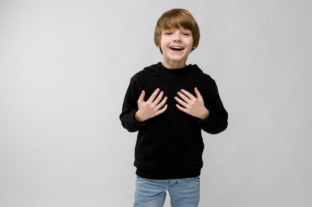 Portrait, de, adorable, smilling, petit garçon, debout, à, mains, sien, poitrine, sur, gris Photo Premium