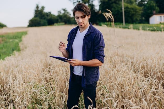 Portrait d'un agronome dans un champ de blé prenant le contrôle du rendement. Photo Premium
