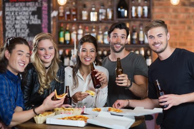 Portrait D'amis Ayant Une Pizza Avec De La Bière Photo Premium